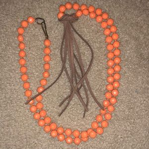 Orange beaded necklace, with brown tassel